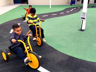 boys on tricycles on playground track