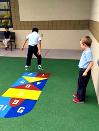one boy plays hopscotch while one watches