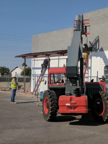 machinery lifts metal canopy framework onto building
