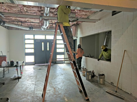 worker on ladder in lobby under construction