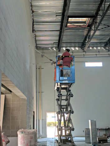 workers spray white paint high on new gym construction wall