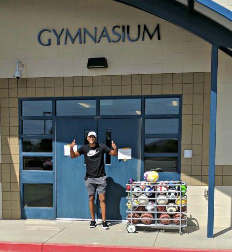 PE teacher wtih full ball cart, two thumbs up under gymnasium sign
