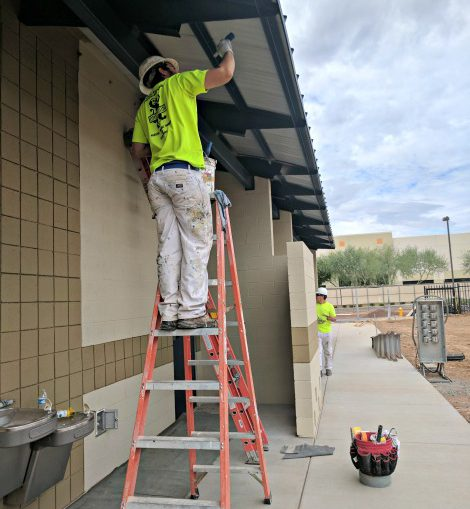 man stands on ladder to paint underside of roof awning