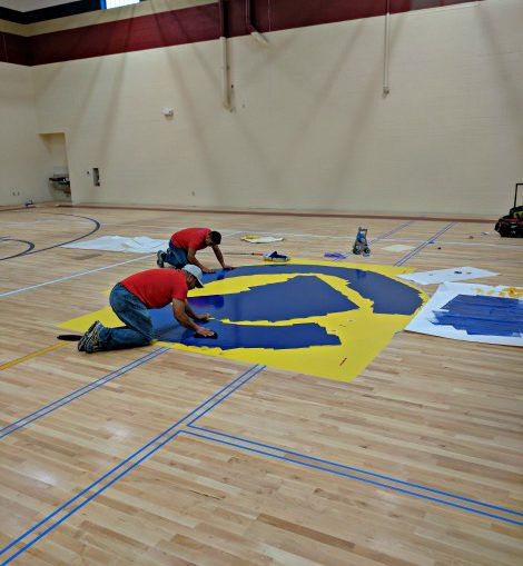 workers in middle of basketball court painting logo