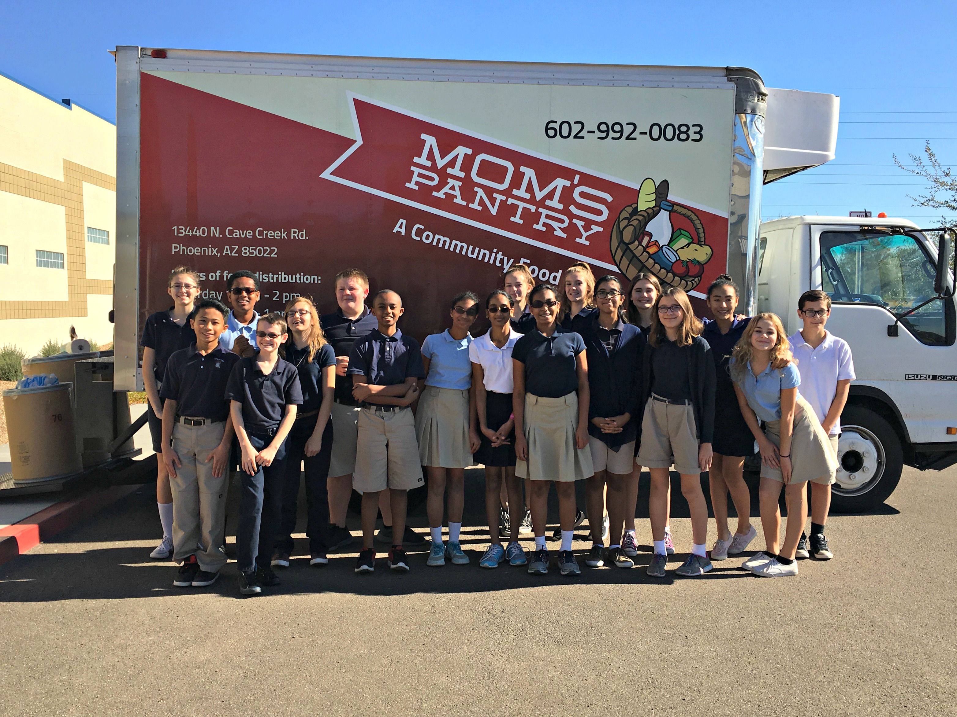 7th grade students in uniforms in front of food pantry truck