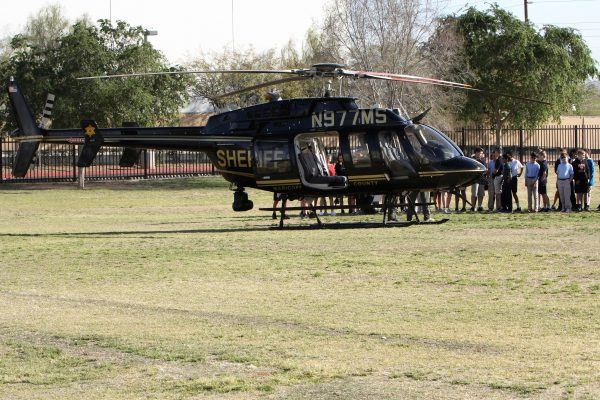 County Sherriff's helicopter on school field with young students lined up to peek inside