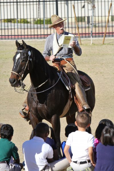 Cowboy historian reads to seated children from the saddle of his horse