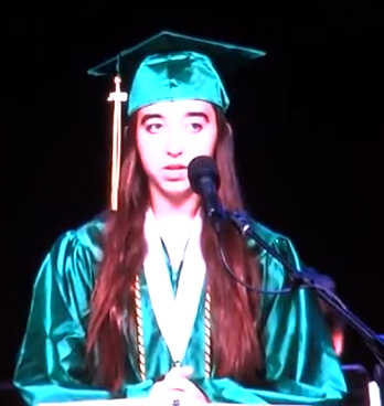 teenage girl with long brown hair in green mortarboard and graduation gown speaking into microphone