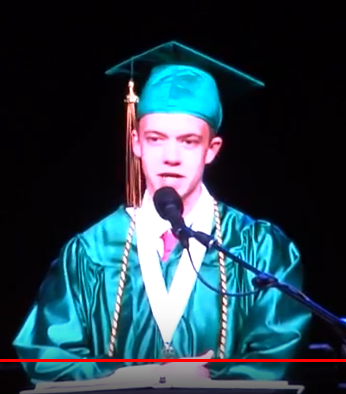 Teenage boy in green mortarboard and graduation gown speaking into microphone