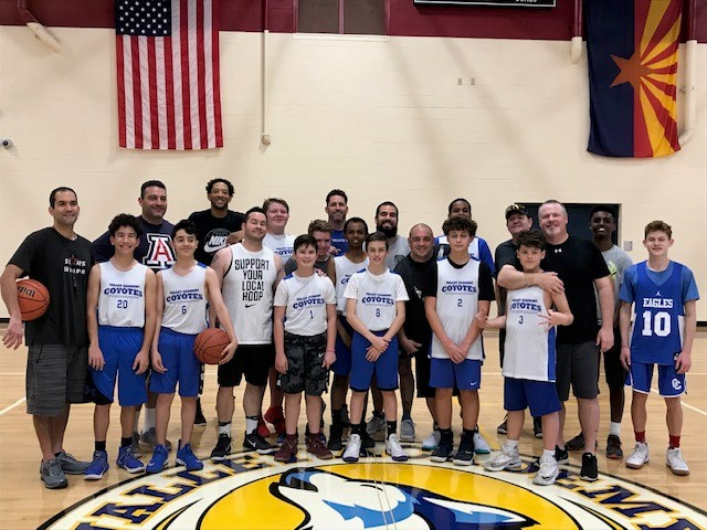 Jr High boys basketball teams posed with their dads on court
