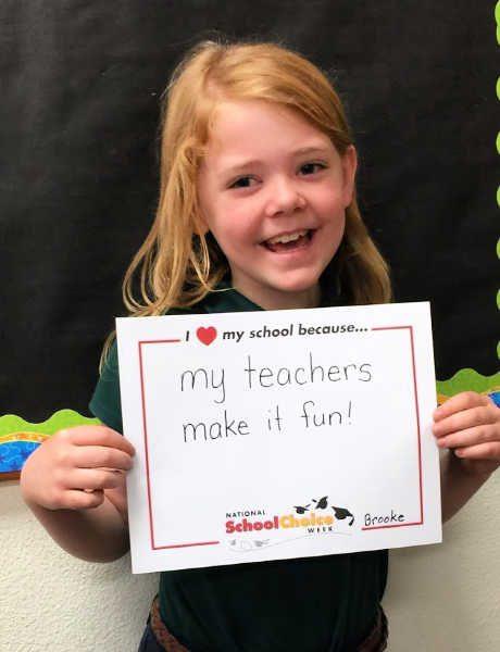 "Smiling kindergarten girl holds sign ""My teachers make it fun"""