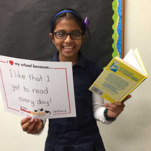 "smiling middle school girl holds book and sign saying ""I like that I get to read every day."""