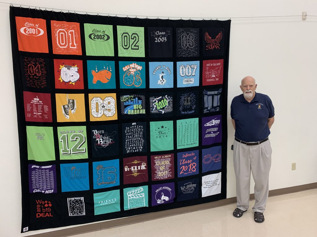 Older male teacher with gray beard stands by quilt constructed from blocks made out of many  school t-shirts