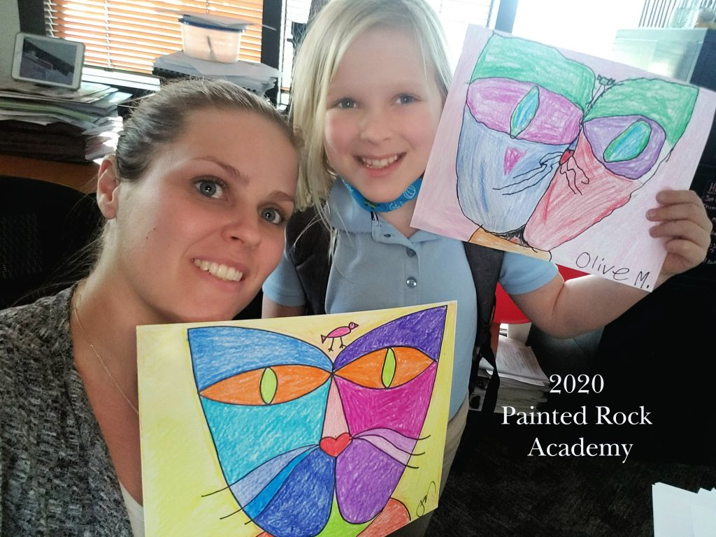Mother and young daughter hold up matching art drawings from online class, labeled Painted Rock Academy 2020